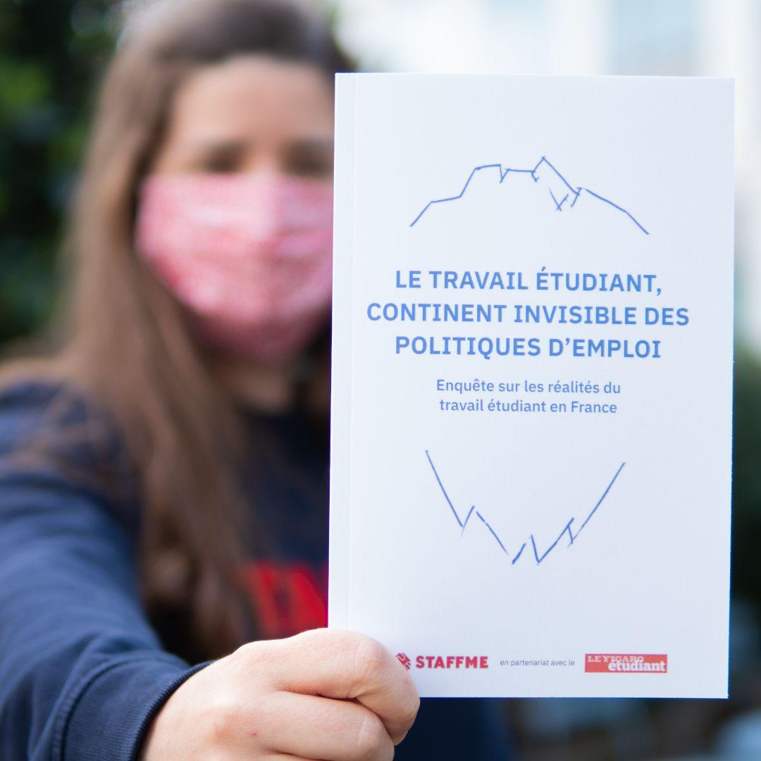 Photo d'une main tenant le livre blanc de StaffMe sur le travail étudiant